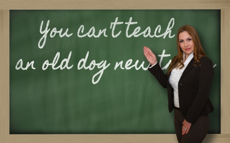 Successful, beautiful and confident woman showing You can t teach an old dog new tricks on blackboard Stock Photo