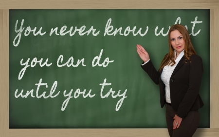 try: Successful, beautiful and confident woman showing You never know what you can do until you try on blackboard