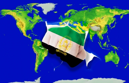 Fist in color national flag of afghanistan punching world map as symbol of export, economic growth, power and success photo