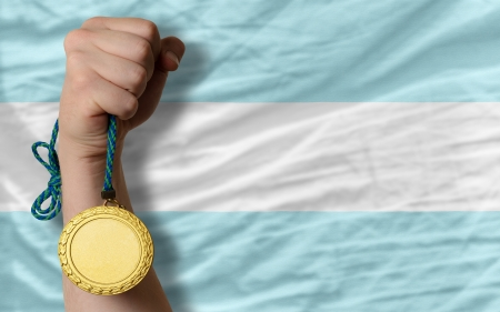 Winner holding gold medal for sport and national flag of argentina photo