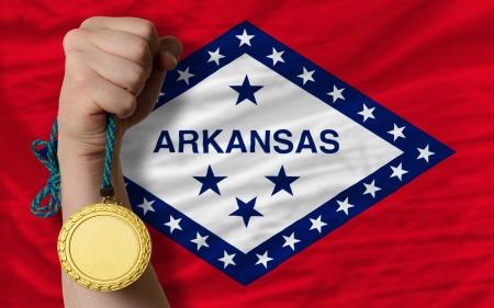 Winner holding gold medal for sport and flag of us state of arkansas