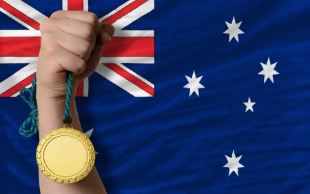 Winner holding gold medal for sport and national flag of australia photo