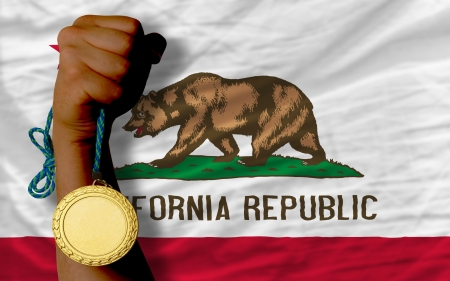 Winner holding gold medal for sport and flag of us state of california Stock Photo