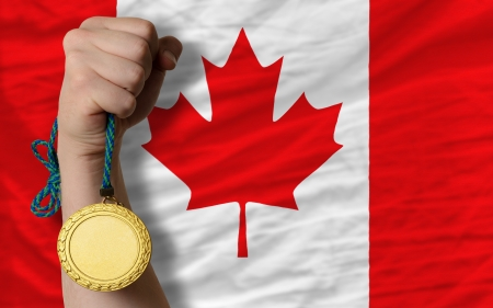 Winner holding gold medal for sport and national flag of canada Stock Photo