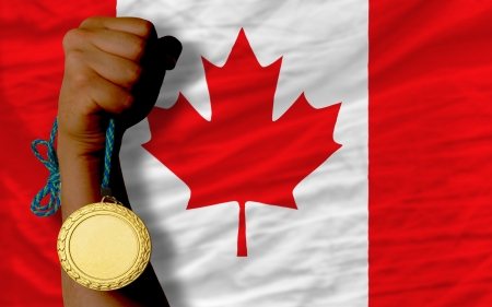 silver medal: Winner holding gold medal for sport and national flag of canada Stock Photo