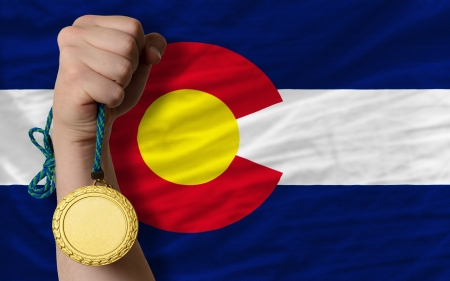 Winner holding gold medal for sport and flag of us state of colorado Stock Photo