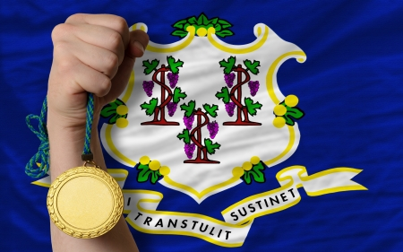 Winner holding gold medal for sport and flag of us state of connecticut