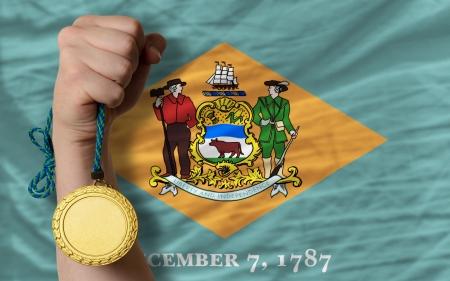 Winner holding gold medal for sport and flag of us state of delaware