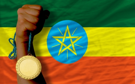Winner holding gold medal for sport and national flag of ethiopia photo