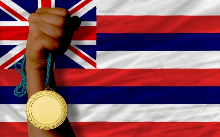 Winner holding gold medal for sport and flag of us state of hawaii Stock Photo