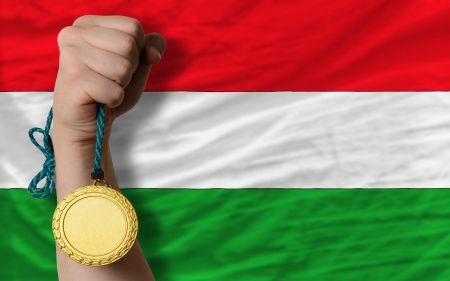 Winner holding gold medal for sport and national flag of hungary photo