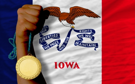 Winner holding gold medal for sport and flag of us state of iowa Stock Photo