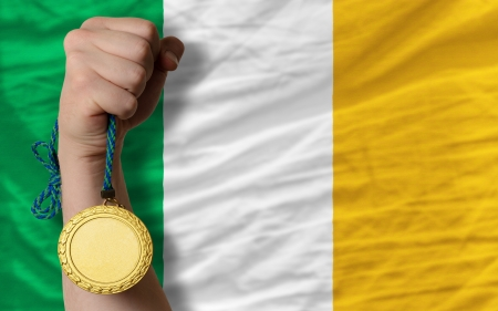Winner holding gold medal for sport and national flag of ireland photo