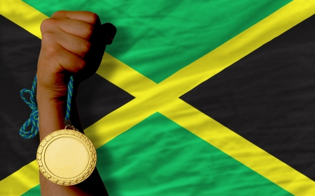 Winner holding gold medal for sport and national flag of jamaica Stock Photo - 20356099