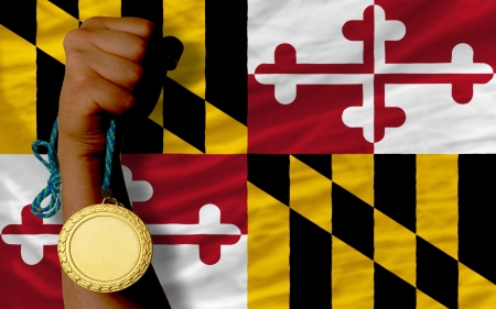Winner holding gold medal for sport and flag of us state of maryland Stock Photo