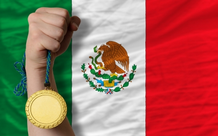 Winner holding gold medal for sport and national flag of mexico
