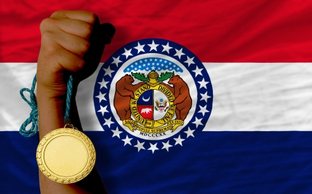 Winner holding gold medal for sport and flag of us state of missouri