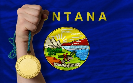 Winner holding gold medal for sport and flag of us state of montana