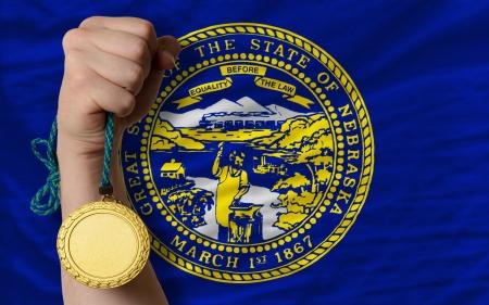 Winner holding gold medal for sport and flag of us state of nebraska Stock Photo