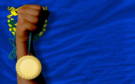 silver medal: Winner holding gold medal for sport and flag of us state of nevada Stock Photo
