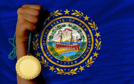 Winner holding gold medal for sport and flag of us state of new hampshire Stock Photo