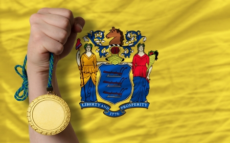 Winner holding gold medal for sport and flag of us state of new jersey Stock Photo