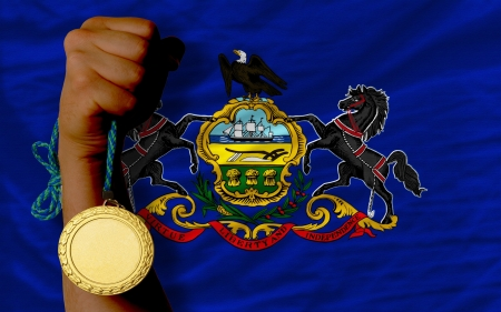 Winner holding gold medal for sport and flag of us state of pennsylvania Stock Photo