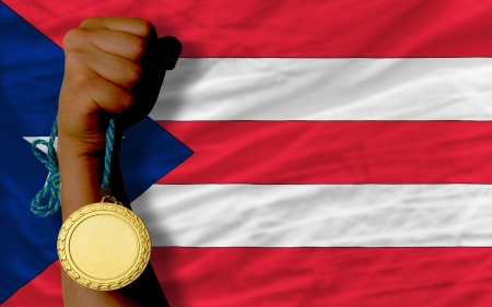 puertorico: Winner holding gold medal for sport and national flag of puertorico