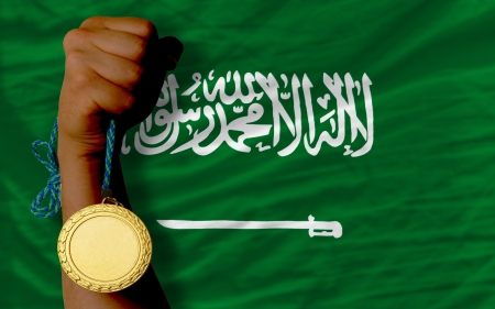 Winner holding gold medal for sport and national flag of  saudi arabia photo