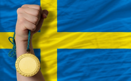 Winner holding gold medal for sport and national flag of sweden photo