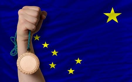 medalist: Holding bronze medal for sport and flag of us state of alaska