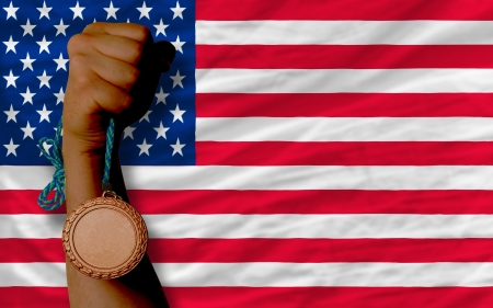 Holding bronze medal for sport and national flag of us