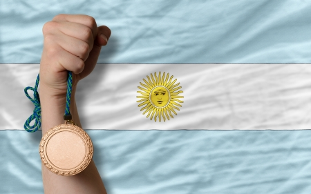 Holding bronze medal for sport and national flag of argentina photo