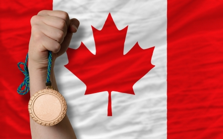 Holding bronze medal for sport and national flag of canada