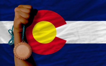 Holding bronze medal for sport and flag of us state of colorado