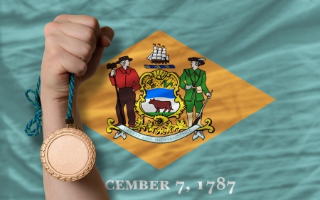 Holding bronze medal for sport and flag of us state of delaware