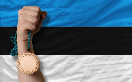 silver state: Holding bronze medal for sport and national flag of estonia