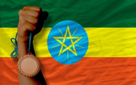 Holding bronze medal for sport and national flag of ethiopia photo