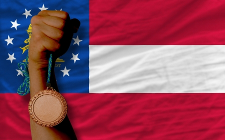 Holding bronze medal for sport and flag of us state of georgia Stock Photo