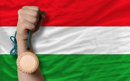 Holding bronze medal for sport and national flag of hungary photo