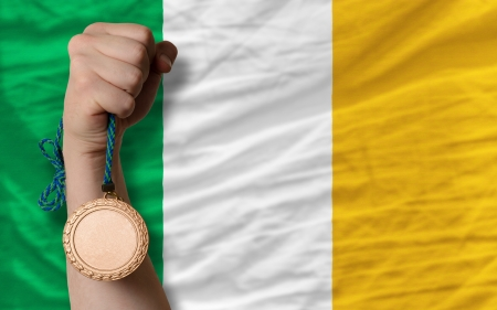 Holding bronze medal for sport and national flag of ireland photo