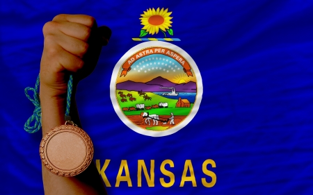 Holding bronze medal for sport and flag of us state of kansas