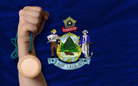Holding bronze medal for sport and flag of us state of maine