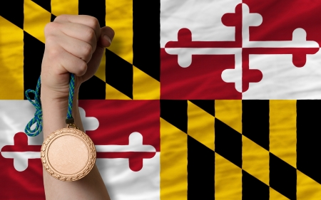 Holding bronze medal for sport and flag of us state of maryland