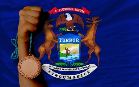 Holding bronze medal for sport and flag of us state of michigan