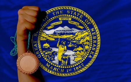 Holding bronze medal for sport and flag of us state of nebraska Stock Photo