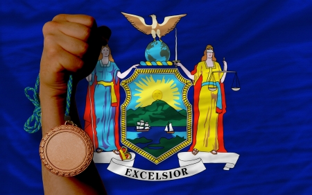 Holding bronze medal for sport and flag of us state of new york