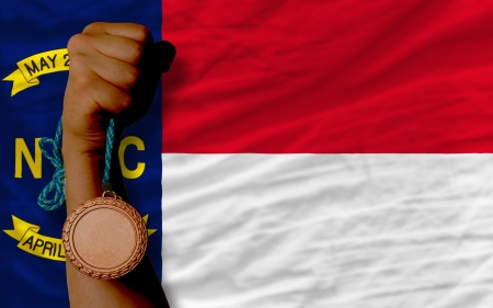 Holding bronze medal for sport and flag of us state of north carolina Stock Photo