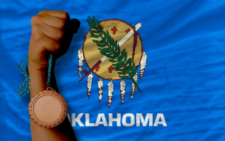 Holding bronze medal for sport and flag of us state of oklahoma Stock Photo