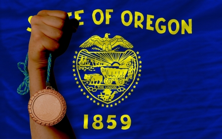 Holding bronze medal for sport and flag of us state of oregon Stock Photo